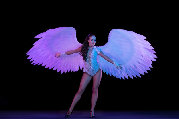 Junge tänzerin mit engelsflügeln im neonlicht auf schwarzer wand