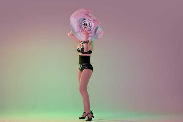 Junge tänzerin mit riesigen blumenhüten im neonlicht auf farbverlauf
