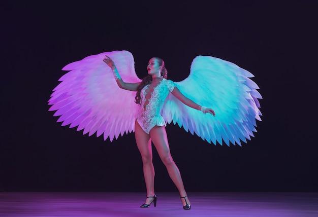 Junge tänzerin mit weißen engelsflügeln in lila blauem neonlicht auf schwarzer wand.