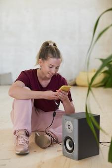 Junge tänzerin sitzt auf dem boden mit ihrem handy und hört musik, während sie im tanzstudio sitzt
