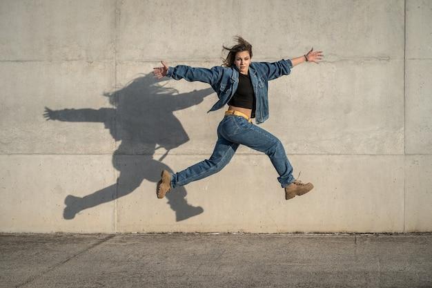Junge tänzerin springen mit grauem hintergrund und reflektiertem schatten. horizontale fotografie