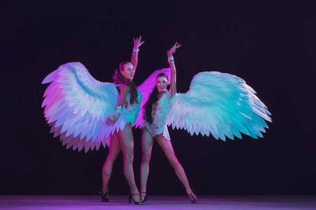 Junge tänzerinnen mit weißen engelsflügeln in neonfarben. anmutige modelle, frauen tanzen, posieren.