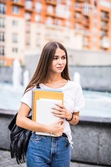 Junge talentierte studentin gekleidet in freizeitkleidung, die durch stadt geht. attraktive brünette frau, die freizeit im freien genießt