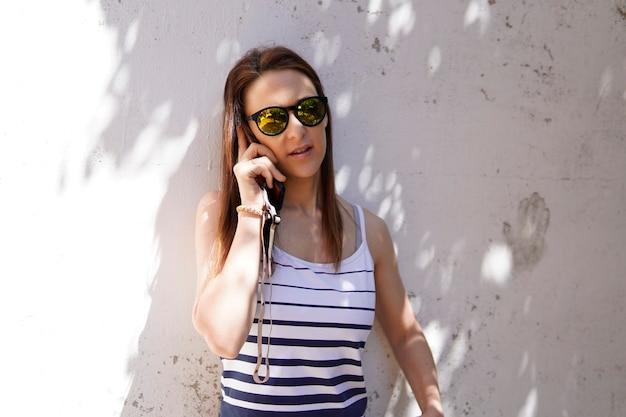 Junge tausendjährige frau unterhält sich an einem sonnigen tag per smartphone
