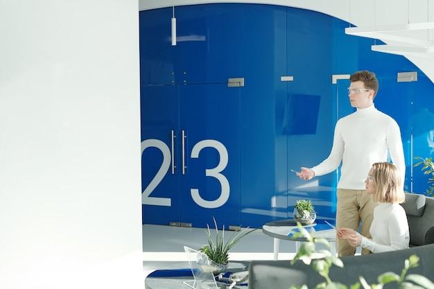 Junge tech-entwickler, die innovative geräte verwenden, während sie in einem futuristischen büro arbeiten