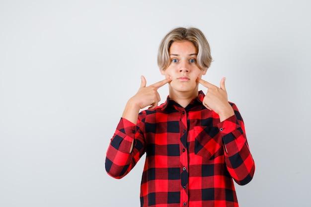 Junge teenager, die finger auf wangen in kariertem hemd drücken und verwirrt aussehen. vorderansicht.