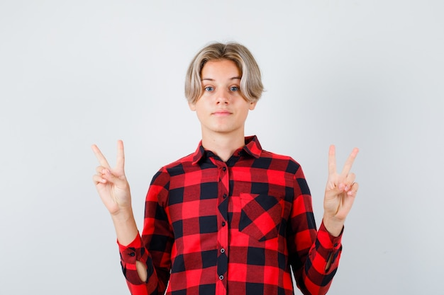 Junge teenager, die friedensgeste in kariertem hemd zeigen und fröhlich aussehen, vorderansicht.