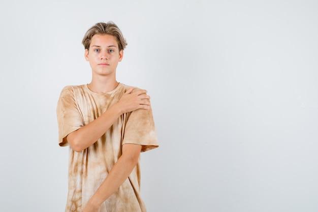 Junge teenager, die hand auf der schulter im t-shirt halten und vernünftig aussehen, vorderansicht.