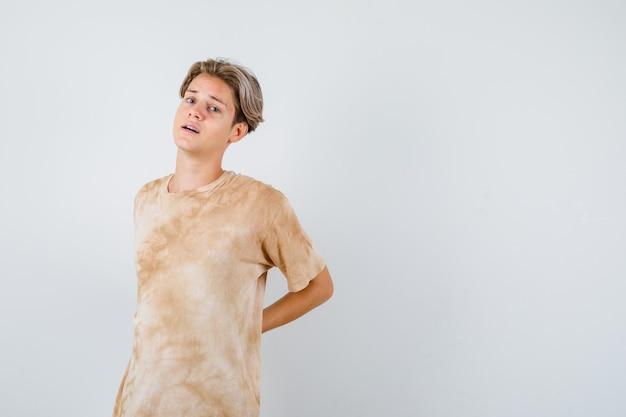 Junge teenager, die im t-shirt unter rückenschmerzen leiden und belästigt aussehen, vorderansicht.