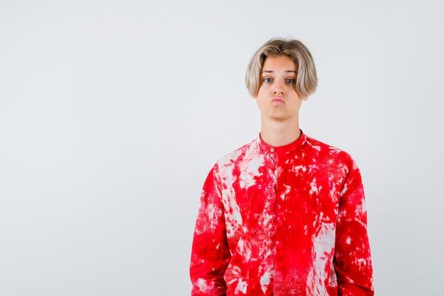 Junge teenager, die lippen im hemd gefaltet halten und enttäuscht aussehen. vorderansicht.