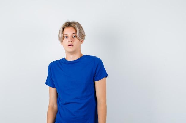 Junge teenager, die vorne im blauen t-shirt suchen und erschrocken aussehen. vorderansicht.