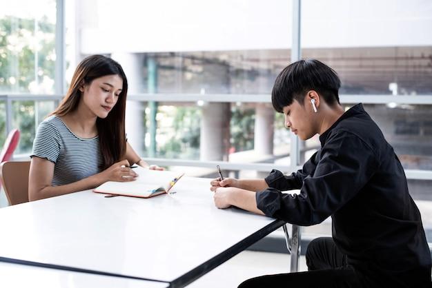 Junge teenager, die zusammen hausaufgaben im besprechungsraum machen
