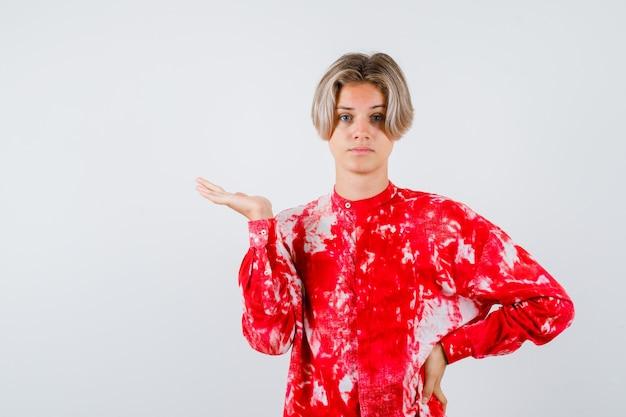 Junge teenager im hemd, die vorgeben, etwas zu halten und selbstbewusst aussehen, vorderansicht.