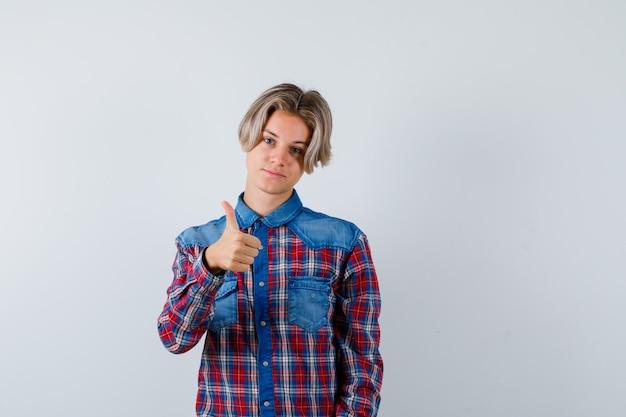 Junge teenager im karierten hemd zeigt daumen nach oben und sieht zufrieden aus, vorderansicht.
