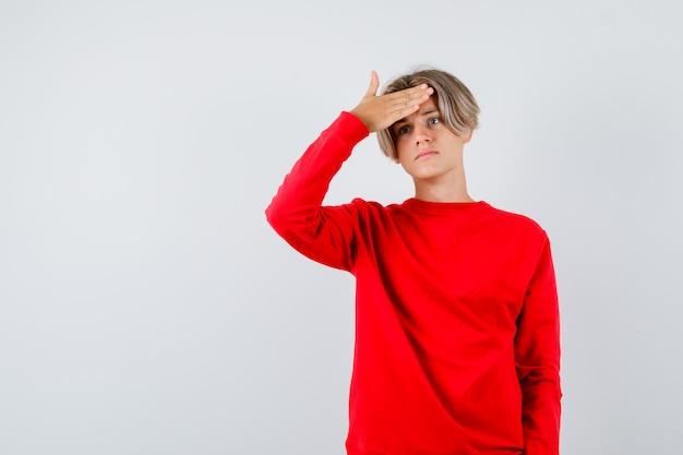 Junge teenager im roten pullover, der fieber hat und verärgert aussieht, vorderansicht.