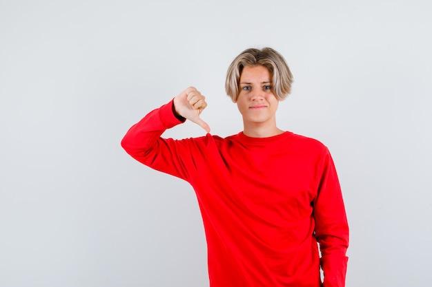 Junge teenager im roten pullover mit daumen nach unten und unzufrieden aussehend, vorderansicht.