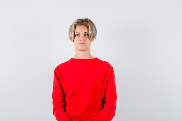 Junge teenager-junge, die im roten pullover wegschaut und verärgert aussieht. vorderansicht.