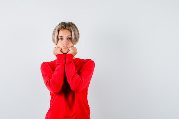 Junge teenager-junge schmollend mit wangen, die sich auf die hände im roten pullover stützen und nachdenklich aussehen, vorderansicht.