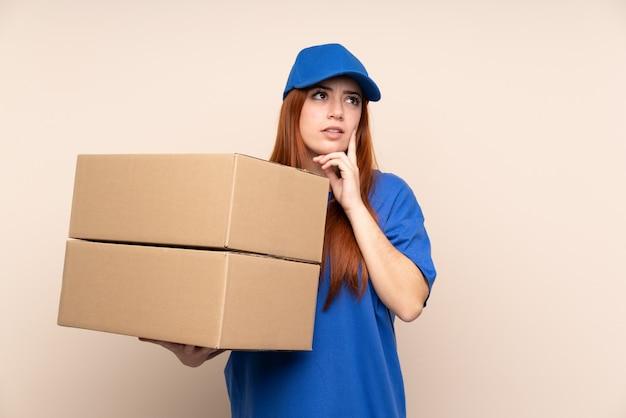 Junge teenager-lieferfrau über isolierte wand, die eine idee denkt