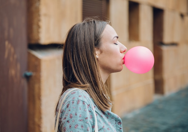 Junge teenager-mädchen bläst rosa kaugummi