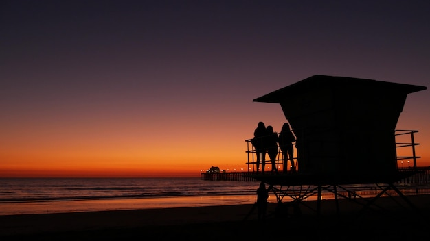 Junge teenager-mädchen silhouetten in der nähe von rettungsschwimmer-turm, freunde am strand des pazifischen ozeans, sonnenuntergang in oceanside, kalifornien usa