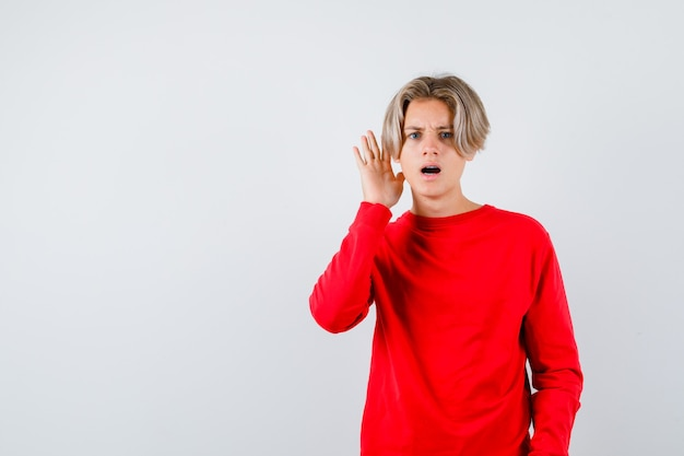 Junge teenager mit der hand in der nähe des ohrs im roten pullover und verwirrt. vorderansicht.