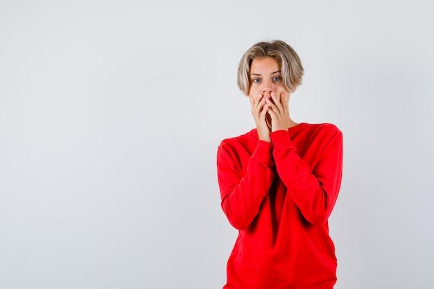 Junge teenager mit händen auf dem mund im roten pullover und ängstlich aussehend. vorderansicht.