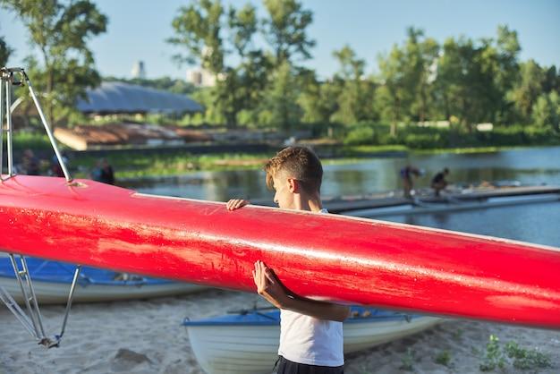 Junge teenager mit sportboot kajak, wassersport