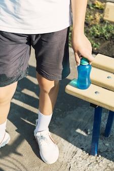Junge teenager trainieren auf dem sportplatz trinkwasser aus der thermosflasche.