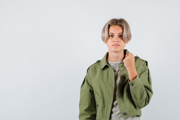 Junge teenager zeigt geballte faust im t-shirt