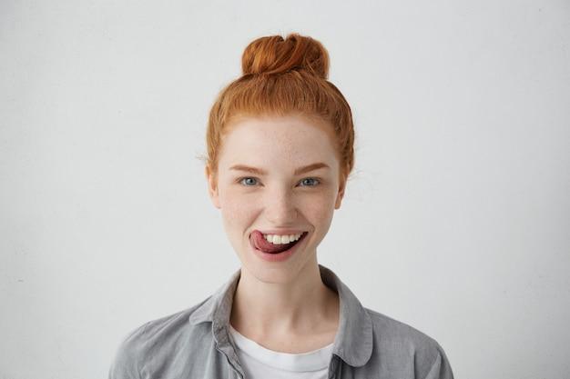 Junge teenagerfrau mit ingwerhaarknoten, die ihre zunge heraushalten, die lustiges aussehen lokalisiert.