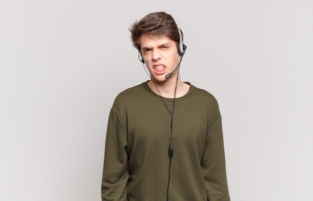 Junge telefonverkäufer, die sich angewidert und irritiert fühlen, die zunge herausstrecken und etwas böses und ekelhaftes nicht mögen