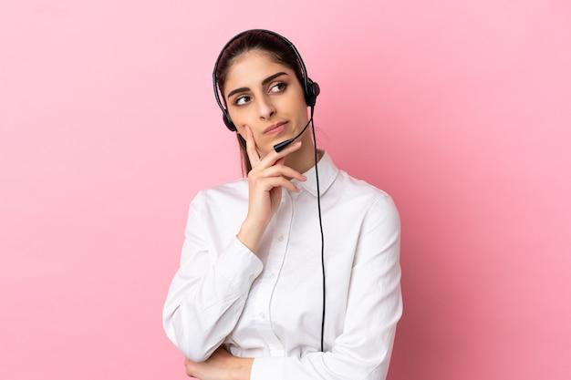 Junge telemarketer über isolierte hintergrund mit zweifeln