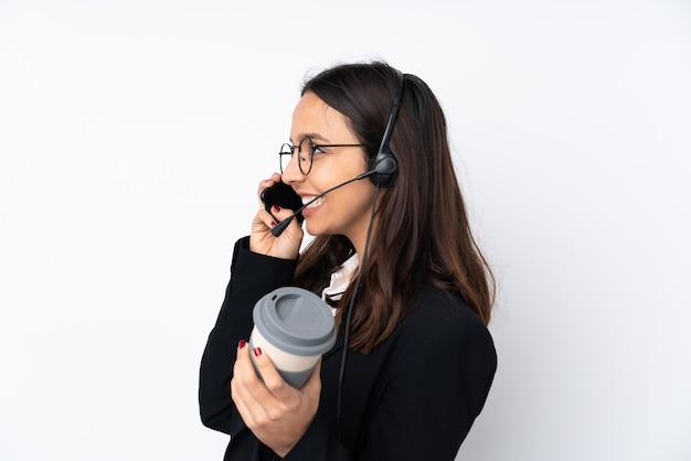 Junge telemarketerfrau auf weißer wand, die kaffee hält, um und ein handy wegzunehmen