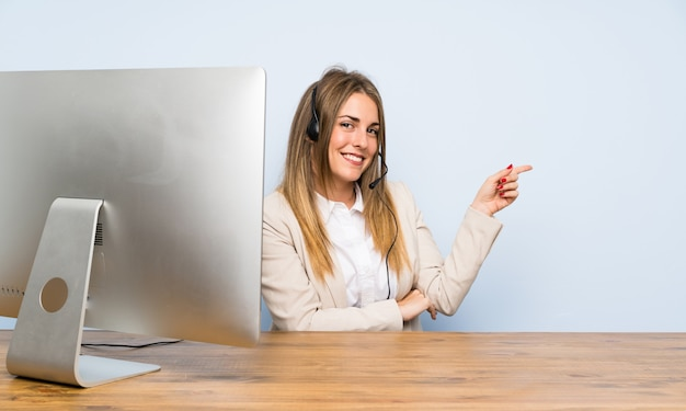 Junge telemarketerfrau, die finger auf die seite zeigt