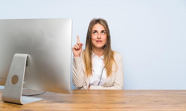 Junge telemarketerfrau, die mit dem zeigefinger eine großartige idee zeigt