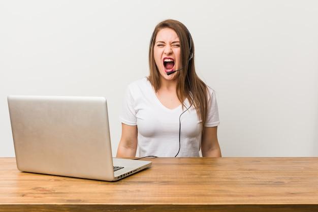 Junge telemarketerfrau, die sehr verärgert und aggressiv schreit.