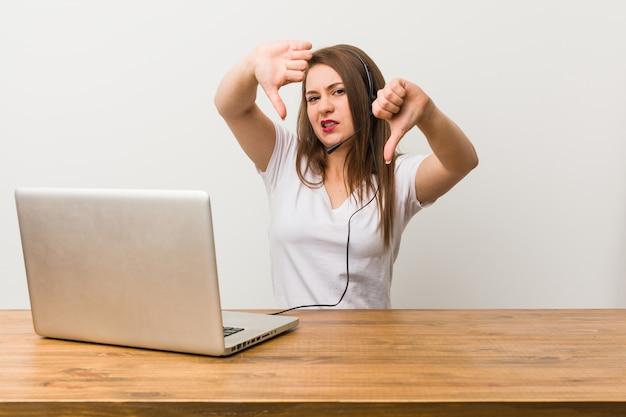 Junge telemarketerfrau, die unten daumen zeigt und abneigung ausdrückt.