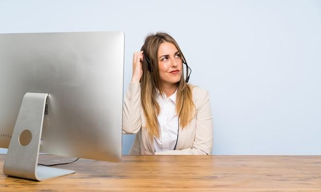 Junge telemarketerfrau, die zweifel und mit verwirrtem gesichtsausdruck hat