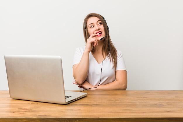 Junge telemarketerfrau entspannte sich und dachte an etwas, das einen kopierraum betrachtete.
