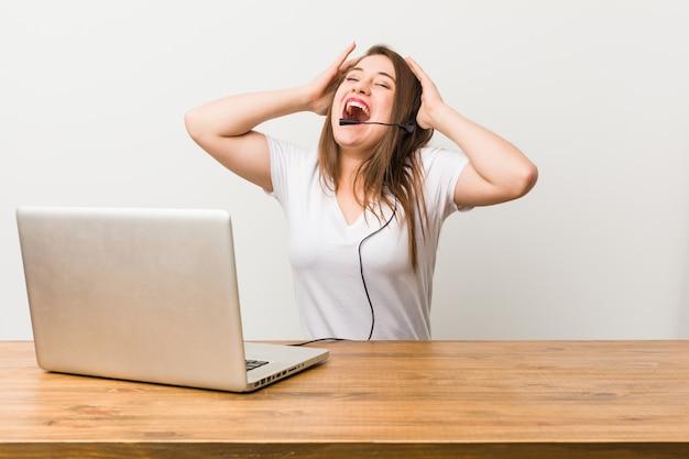 Junge telemarketerfrau lacht froh, hände auf kopf halten