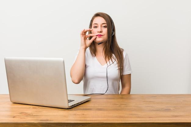 Junge telemarketerfrau mit den fingern auf den lippen, die ein geheimnis halten.
