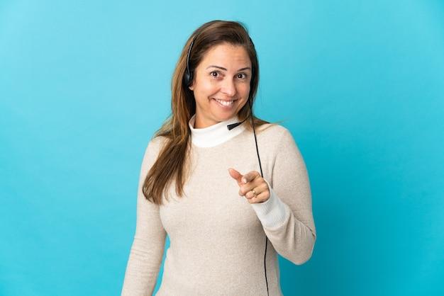 Junge telemarketerfrau über isoliertem blau überrascht und nach vorne zeigend