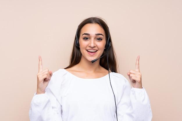 Junge telemarketerfrau über lokalisiertem eine großartige idee oben zeigen