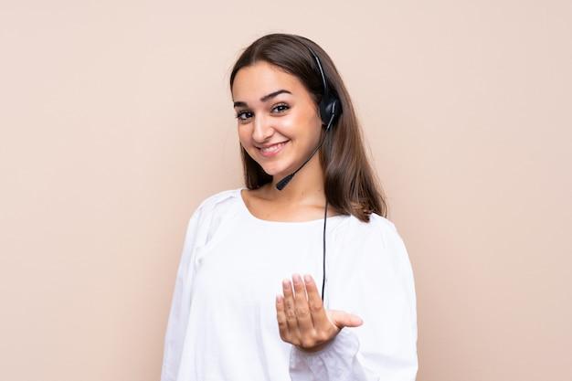 Junge telemarketerfrau über lokalisierter einladung, mit der hand zu kommen. schön, dass sie gekommen sind