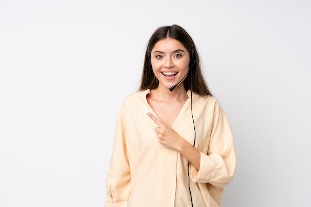 Junge telemarketerfrau über lokalisierter weißer wand finger auf die seite zeigend