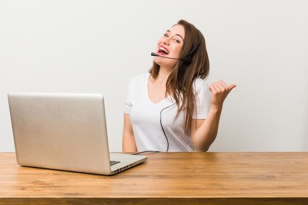 Junge telemarketerfrau zeigt mit dem daumenfinger weg, lachend und sorglos.
