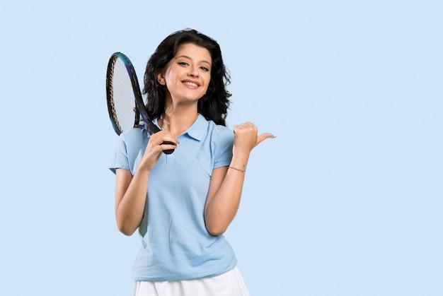 Junge tennisspielerfrau, die auf die seite zeigt, um ein produkt über lokalisierter wand darzustellen