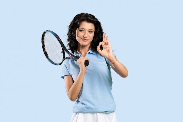Junge tennisspielerfrau, die okayzeichen mit den fingern zeigt