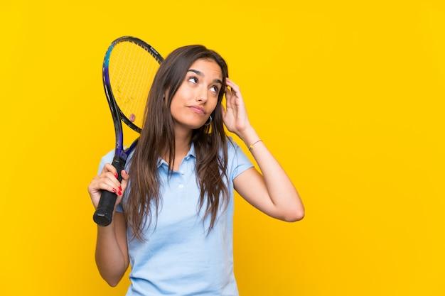 Junge tennisspielerfrau, die zweifel und mit verwirrtem gesichtsausdruck hat